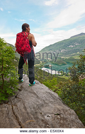 Female climber looking down over lake Tablino and castle, Sarche, Trentino, Italy - Stock Photo