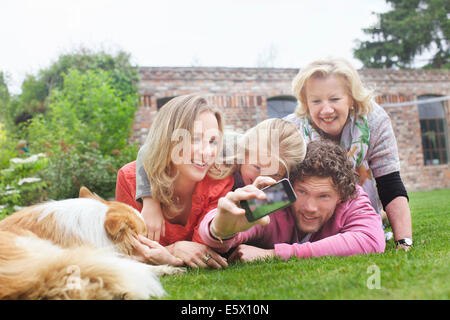 Father photographing family lying on lawn - Stock Photo