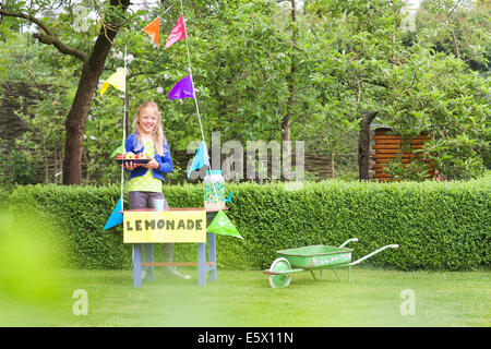 Lemonade stand girl with tray of apples behind her stand - Stock Photo