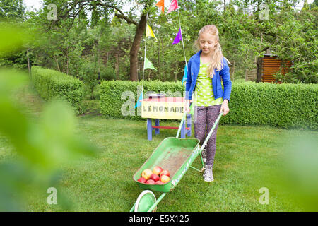 Lemonade stand girl carting apples away from her stand - Stock Photo