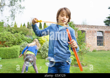SIblings playing with soap bubbles in garden - Stock Photo