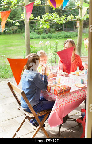 Mother chatting with children at patio table - Stock Photo