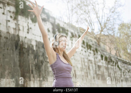 Happy young woman, wearing headphones and raising arms