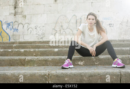 Sporty young woman sitting on steps - Stock Photo