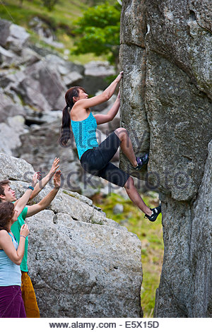 Mature female climber bouldering on RAC boulders, watched by friends, Snowdonia, North Wales, UK - Stock Photo