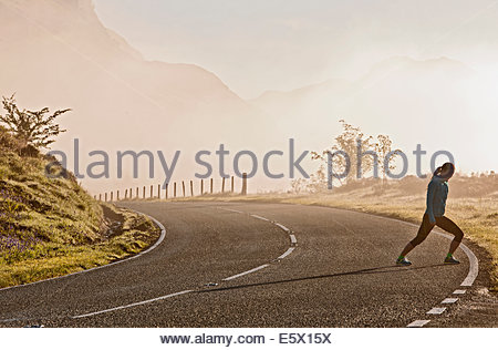 Female runner warming up on roadside, Capel Curig, Snowdonia, North Wales, UK - Stock Photo