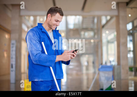 Male cleaner texting on smartphone in office atrium - Stock Photo