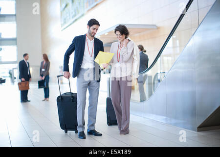 Businessman and businesswoman arriving in conference centre atrium - Stock Photo