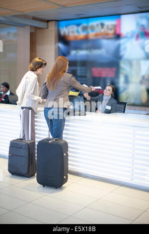 Two businesswoman checking in at conference centre - Stock Photo