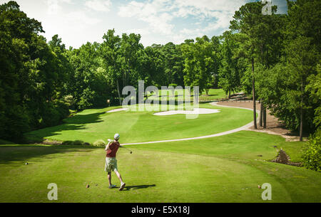 Elevated view of young male golfer teeing off on golf course, Apex, North Carolina, USA - Stock Photo