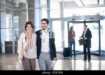 Young businessman and businesswoman arriving at conference centre - Stock Photo