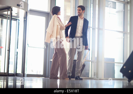 Young businesswoman and businessman arriving at conference centre - Stock Photo