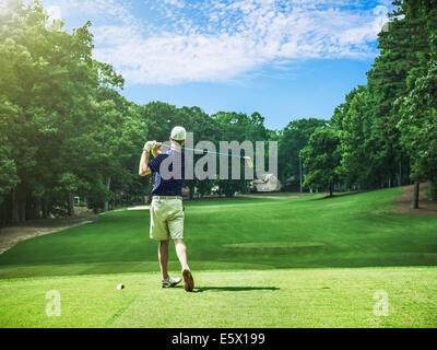 Rear view of young male golfer teeing off on golf course, Apex, North Carolina, USA - Stock Photo