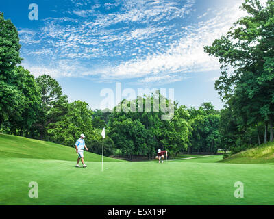 Two young male golfers competing on golf green, Apex, North Carolina, USA - Stock Photo