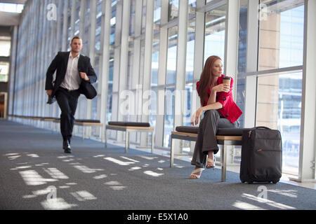 Businessman running along conference centre corridor - Stock Photo