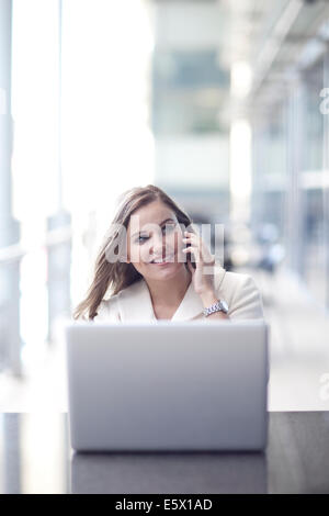 Young businesswoman using laptop and chatting on smartphone in conference centre - Stock Photo