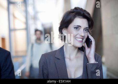 Young businesswoman chatting on smartphone in conference centre - Stock Photo