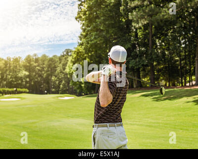 Rear waist up view of young male golfer teeing off on golf course, Apex, North Carolina, USA - Stock Photo