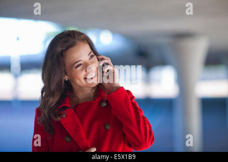 Young woman chatting on smartphone in city underpass - Stock Photo