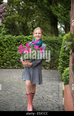 Portrait of girl with flower pot plant in garden - Stock Photo