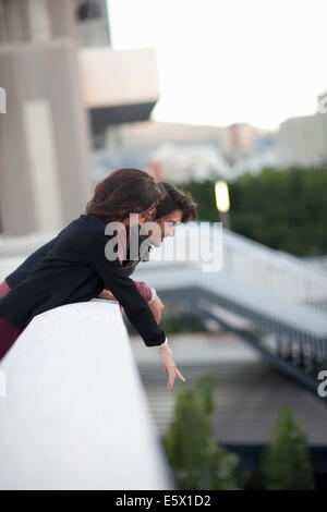 Couple looking down and pointing from city rooftop - Stock Photo