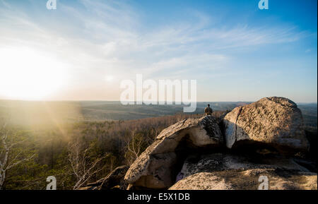 Young male hiker on top of rock formation - Stock Photo