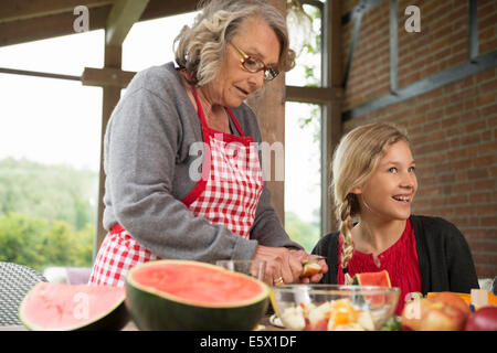 Girl and grandmother at kitchen table learning to slice fresh fruit - Stock Photo