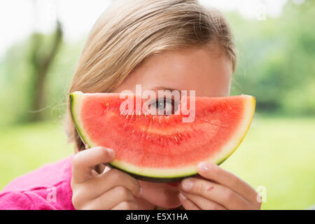 Close up portrait of girl peering through watermelon slice - Stock Photo