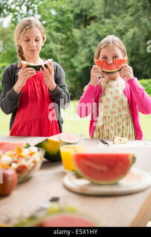 Two sisters at patio table eating and holding up watermelon slice - Stock Photo