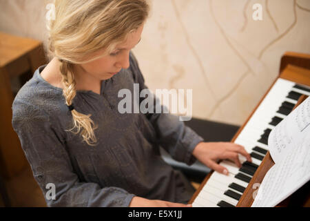 Girl playing the piano in dining room - Stock Photo