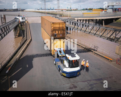 Elevated view of shipping container and truck on ramp to ship - Stock Photo
