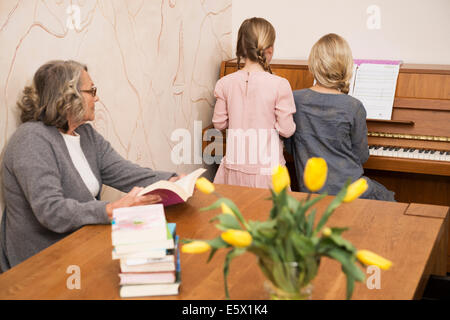 Two sisters playing piano watched by grandmother - Stock Photo
