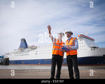 Port workers with ship in port - Stock Photo