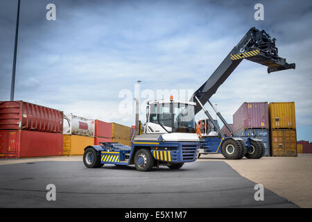 Truck stacking shipping containers in port - Stock Photo