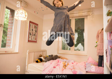 Girl jumping mid air from bed in bedroom - Stock Photo