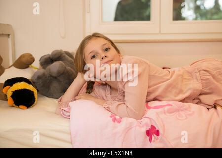Portrait of mischievous girl lying on bed - Stock Photo