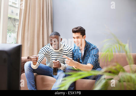 Two young men drinking beer and watching TV in living room - Stock Photo