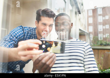 Two young male friends taking selfie behind patio glass - Stock Photo