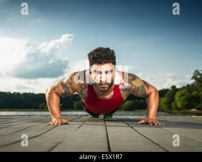 Surface level portrait of young man doing push ups on lake pier - Stock Photo