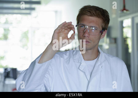 Young male scientist holding up pill in lab - Stock Photo