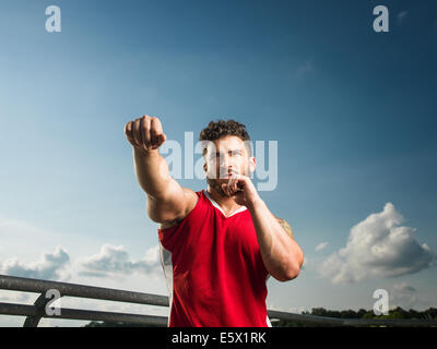 Low angle portrait of young male boxer training - Stock Photo