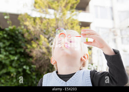 Young boy blowing bubbles in garden - Stock Photo