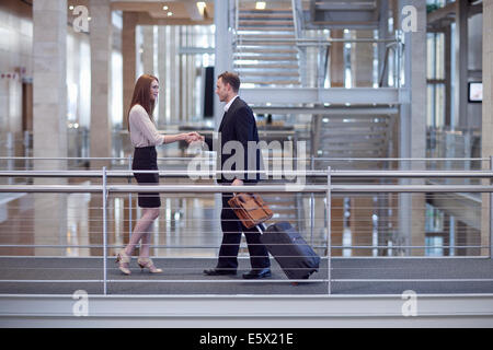 Mid adult businesswoman greeting businessman on conference centre walkway - Stock Photo