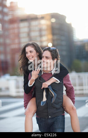Mid adult man giving girlfriend piggyback in street - Stock Photo