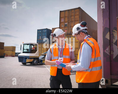 Port workers and shipping containers in port - Stock Photo
