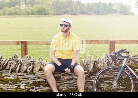 Cyclist sitting on stone wall, Cotswolds, UK - Stock Photo