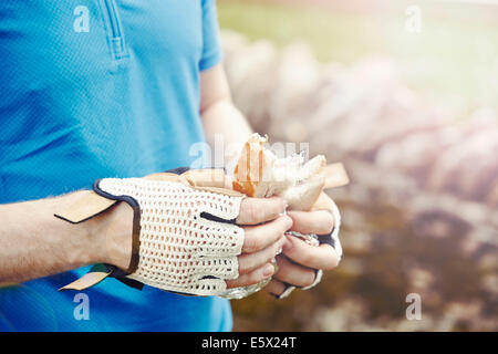 Cyclist holding sandwich with gloved hands - Stock Photo