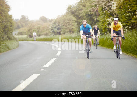Cyclists riding on single carriageway, Cotswolds, UK - Stock Photo