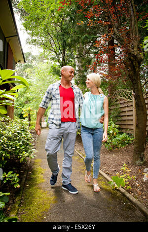 Happy couple strolling in garden - Stock Photo