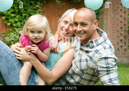 Portrait of happy couple sitting with toddler daughter in garden - Stock Photo